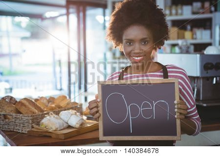 Smiling waitress holding chalkboard with open sign in cafe