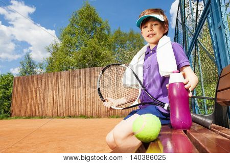 Portrait of tennis player, young boy with water bottle, having rest sitting on the bench after tennis game