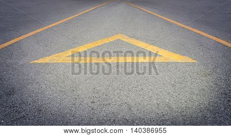Yellow Arrow direction on a rough road with copy space in the bottom