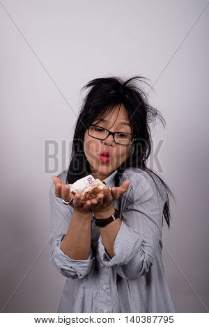 Asian woman with bright lipstick and ruffled hair holding money
