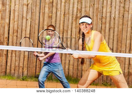 Mixed double tennis partners, active young women, waiting for ball, hitting on clay court