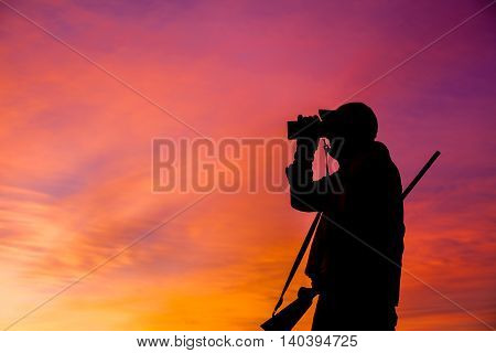 a deer hunter with rifle silhouetted at sunrise