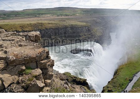 Photo of a waterfall as it falls into a river
