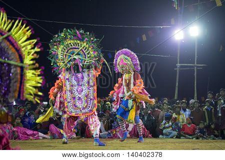 BAMNIA PURULIA WEST BENGAL INDIA - DECEMBER 23RD 2015 : Dancer dressed as Hanumanji is killing monster Chhau Dance festival. It is a very popular Indian tribal martial dance performed at night amongst spectators.