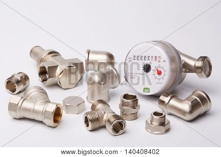 New water meter with fittings  on a white background. Sanitary equipment.