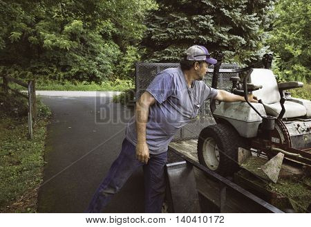 Man loading lawnmower on trailer with gate in the background in Virginia.