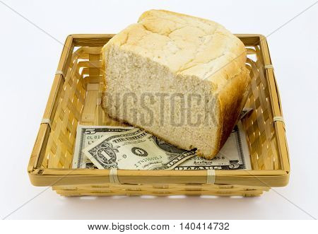 5 and 1 dollar notes with half a loaf of white bread in basket isolated on white