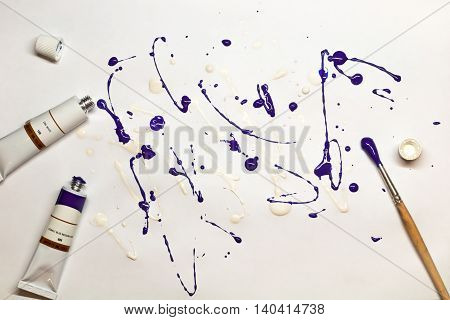 Artistic expression. Blots of purple and white paint on a sheet of paper with a brush and oil color tubes lying near it. Abstract painting