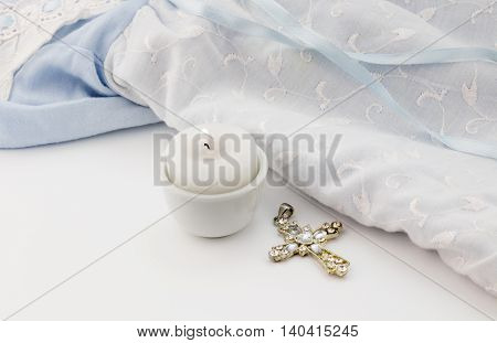 Christening background with cross pendant lit candle and blue baby outfit