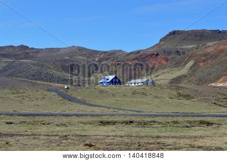 Photo of a single house and barn with a backdrop of mountains and clear blue sky