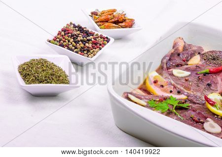 Steaks of red meat marinated with emulsion of lemon juice and olive oil and seasoned with pepper of various colors fresh thyme and parsley hot pepper and finally Barolo or a high good red wine