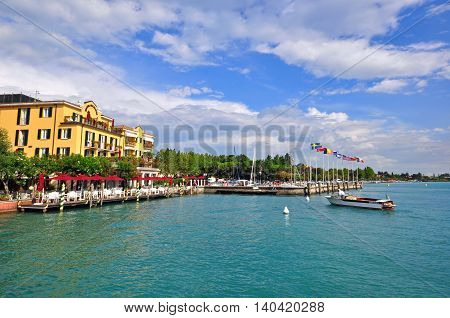 SIRMIONE ITALY - JULY 14: View of a harbor with cafes and restaurants in Sirmione Italy on July 14 2014. Sirmione is a resort on Garda lake in northern Italy.