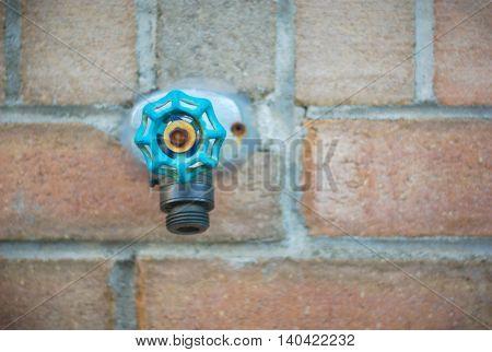 tap water spigot on brick wall, aqua blue green valve