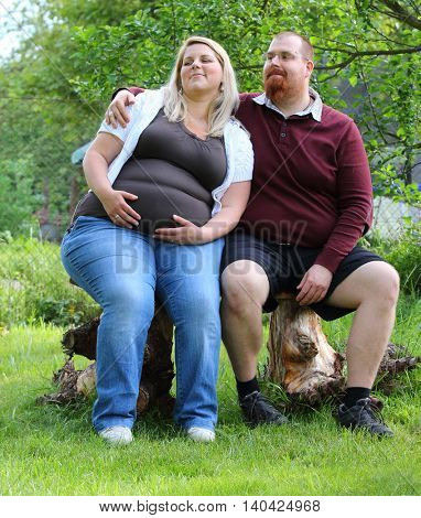 Overweight couple. Healthy lifestyle concept. Obese adults on garden bench. Happy family together.