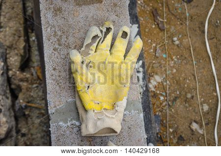 old torn dirty worker hand gloves deserted on concrete ground