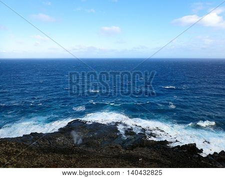 Water sprays out of blowhole on lava rock shore with ocean on the horizon at Makapuu point on Oahu Hawaii. 2016.