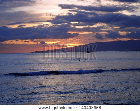 Dramatic Sunset dropping behind the Waianae Mountain range with clouds waves and boats on the Pacific ocean off the coast of Oahu Hawaii.