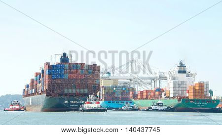 Oakland CA - July 27 2016: The Port of Oakland is the fifth busiest container port in the United States. Tugboats assist APL TOURMALINE and SEASPAN CHIWAN maneuver to the dock.
