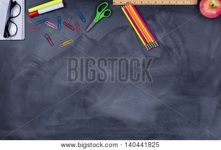 Back to school concept with student supplies on upper part of chalkboard.