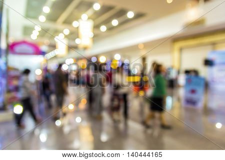A blurred photo of people walking in exhibition hall Use for as background.