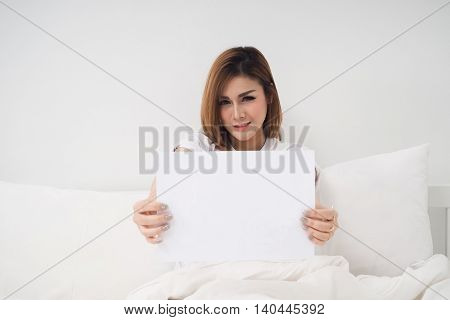 Asian woman sitting on white bed and holding blank paper in bedroom.