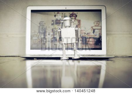 vintage silver robot watching a film on a laptop