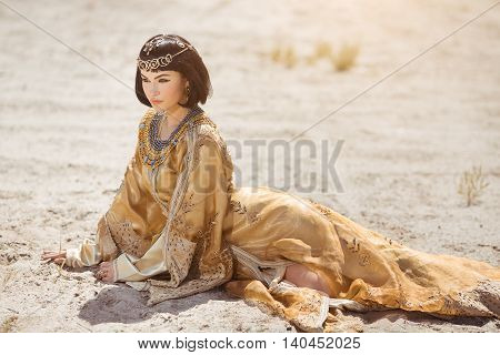 Fashion stylish beauty woman with black short haircut and professional make-up of Cleopatra. Girl sitting in golden dress outdoors in desert. Hot sunny weather.
