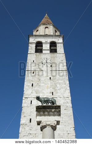 Church steeple in front of capitoline wolf column