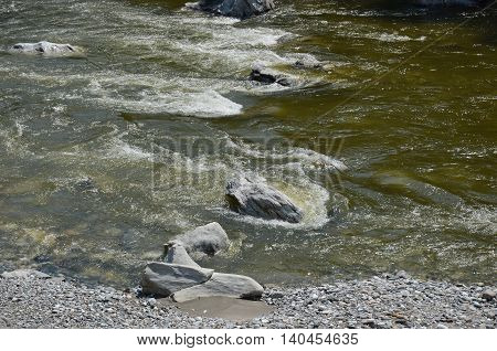Clear water of Irkut River in its beginning in the Sayan Mountains in sunny day