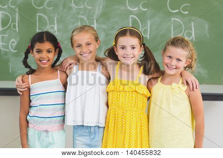 Portrait of smiling kids standing with arm around in classroom at school