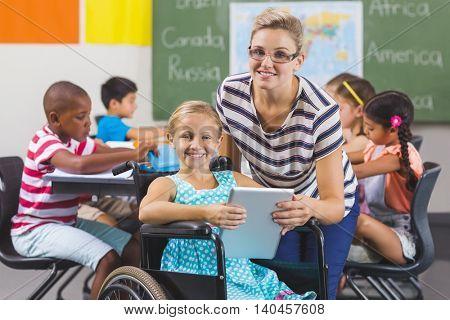 Smiling schoolgirl and teacher using digital tablet in classroom at school
