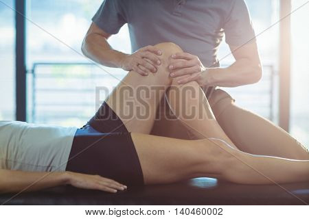 Physiotherapist giving knee therapy to a woman in clinic