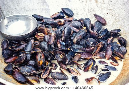 Steamed mussels in white wine sauce cooking at large metallic pan. Fresh mussels at grill pan. Seafood barbecue outdoors. Picnic healthy food, mussels in shells. Stewed clams, mediterranean cuisine.