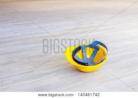 Yellow construction industrial helmet on floor made of laminate with wooden color.