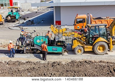 Zrenjanin Vojvodina Serbia - September 14 2015: Excavator with his lifted bucked is transporting asphalt from dumper truck to decanting into tarmac road laying machine at construction site.