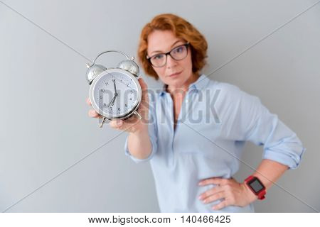 It is high time. Close up of alarm clock in hands of pleasant serious senior woman holding it and looking at you while standing isolated on grey background