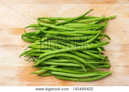 green string beans on a wooden chopping board
