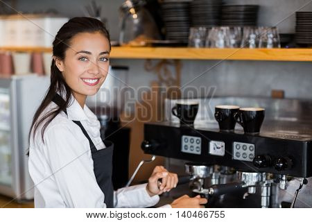 Portrait of smiling waitress making cup of coffee at cafe