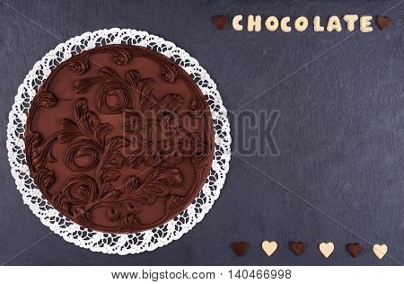 Round Chocolate cake on a slate board top view. Chocolate chocolate letters with text chocolate and copy space