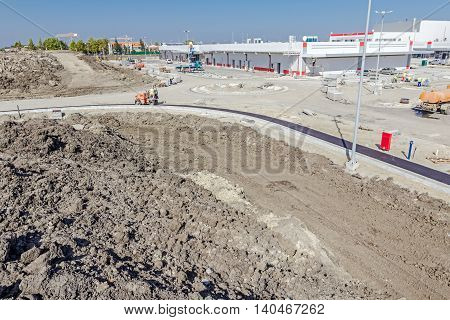 Hot asphalt is spreading machine during road construction. Landscape transform into urban area with machinery people are working. View on construction site.