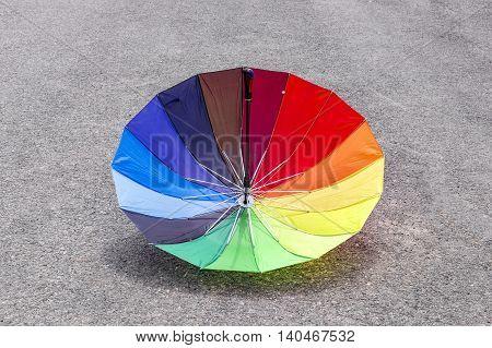 Reversed multicolored umbrella inverted on the road.