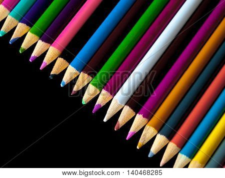 Pencil crayons lying in a line on a dark coloured table.