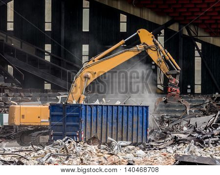 Yellow excavator demolishing a former sports stadium