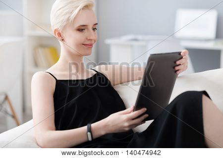 Lets look here. Clever young woman sitting on the couch and using a tablet for choosing something