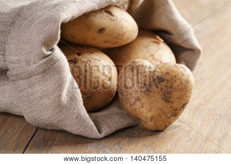 sack full of organic potatoes on oak wooden table, shallow focus
