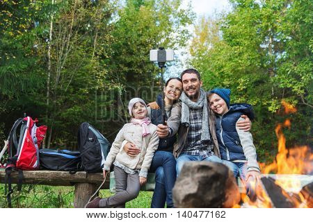 camping, travel, tourism, hike and people concept - happy family sitting on bench and taking picture with smartphone on selfie stick at campfire in woods
