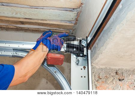 Garage doors installation.Worker installing; lifting system in metal profil with screwdriver