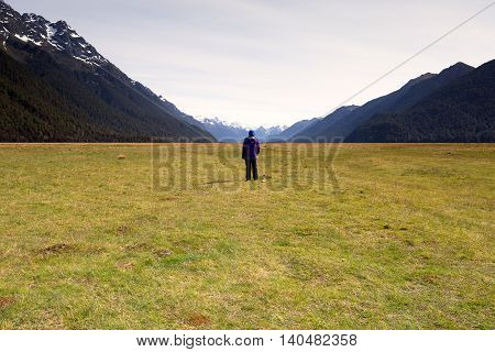 A girl standing and facing a vast empty landscape.