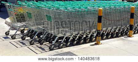 three rows of shopping carts with blue-greenish plastic covered, handles in a parking lot behind yellow and black bumper posts, hedge of red Indian jasmine flowers behind the carts, Songkhla, Thailand