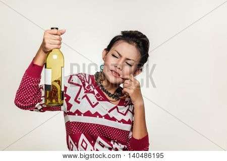 Asian woman holds up an empty bottle mood wondering.
